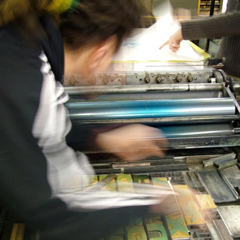 Pat Randle adjusting the letterpress forme, on the bed of a Western proofing press.