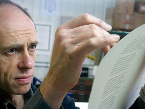Phil Abel examining and marking the back of the sheet, for an areas where impression needs to be reduced.
